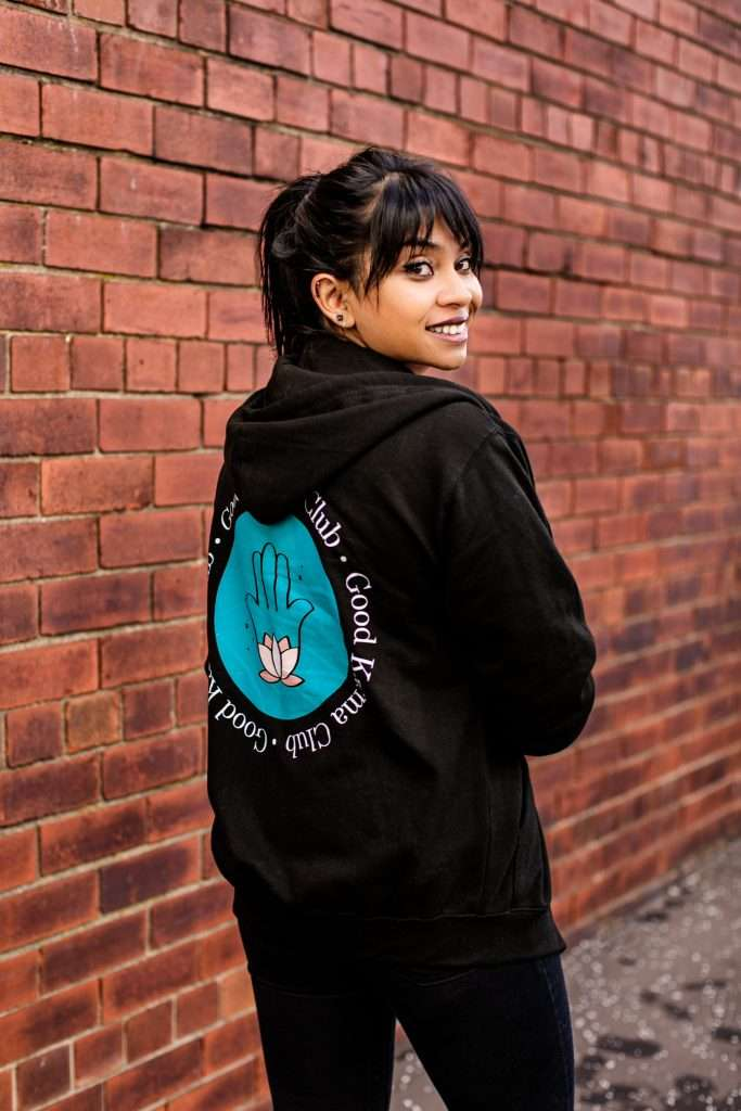 Rugina, Female Entrepreneur, during her personal branding photoshoot. Rugi is stood in front of a red brick wall facing away from the camera but looking back over her right shoulder. She is wearing a black hoody with the GKC logo (Hamsa hand with lotus) on the back.