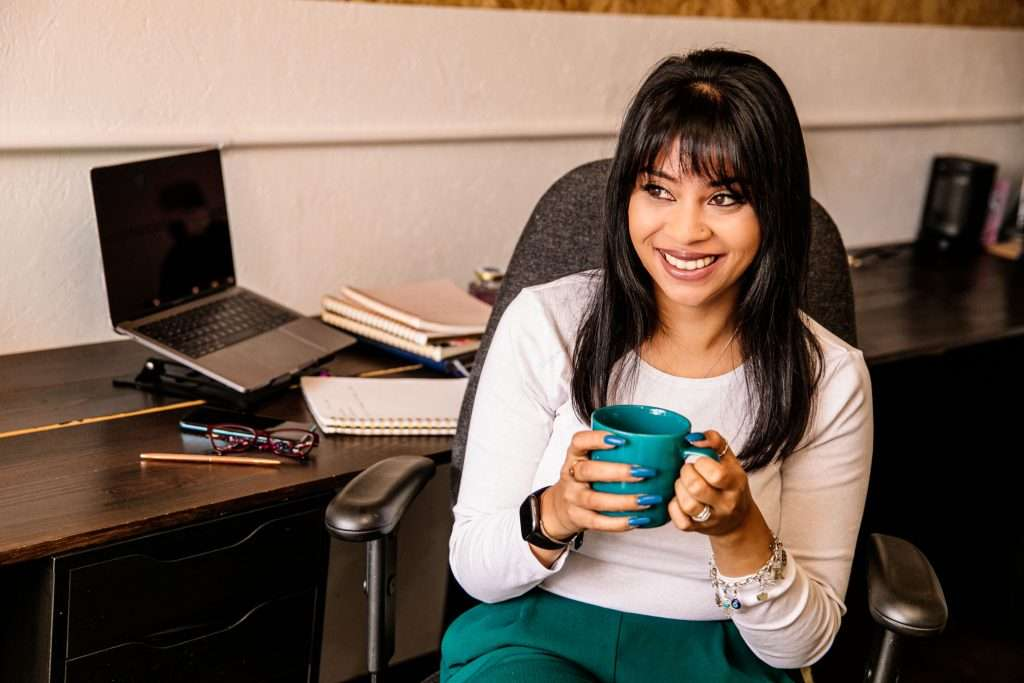 Rugi taking a tea break during her personal branding shoot. She is sat in a black office chair and looking to the left of the photo. She is wearing a white long sleeved top and holding a turquoise mug of tea. In the background is a desk and laptop.
