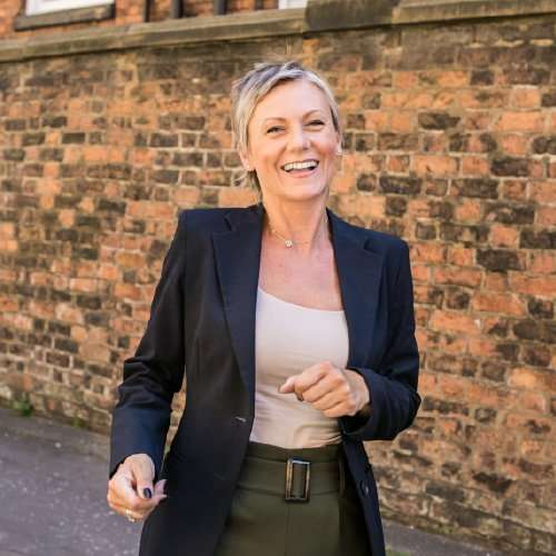 Our client Trisha during her logo design and photoshoot project in Manchester. Behind Trisha is a red brick wall and she is walking forwards and smiling. Trisha is wearing a dark blue suit jacket, a white vest top and olive green trousers.