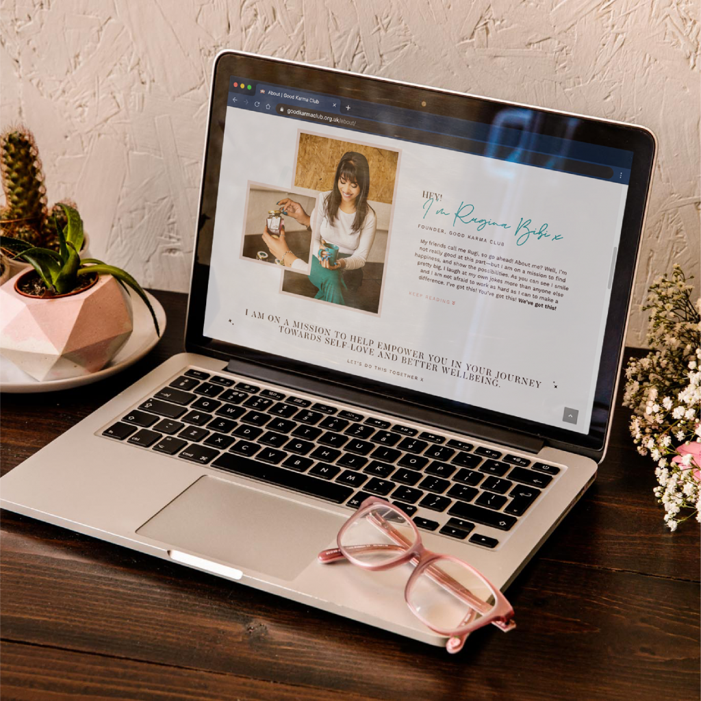 A mockup of Rugi's branding and website design on a laptop. The website is shown on a Macbook. Next to the laptop are pink glasses and two catci.
