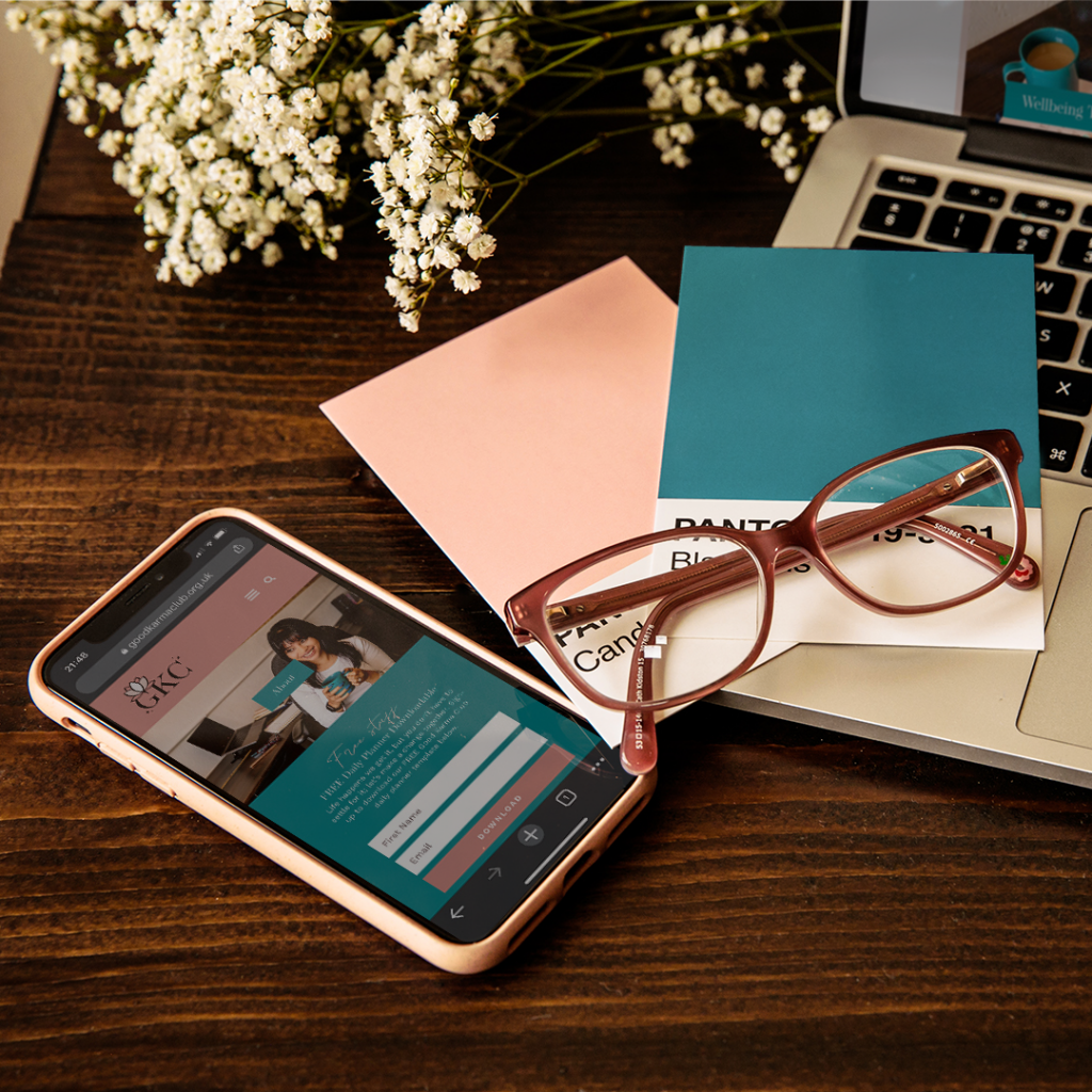 A mockup of Rugi's branding and website design in mobile view. The website is shown on an iPhone XR laid on a desk. Next to the phone are pink glasses and Pantone swatches used in the branding process.