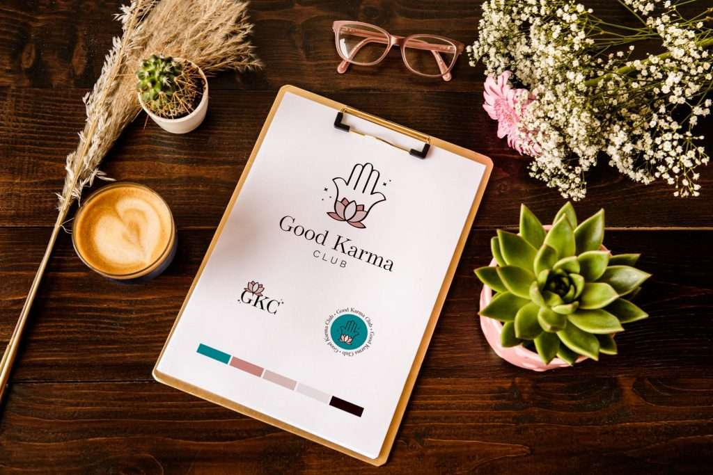 A professional branding example by That's Her Business. A wooden clipboard show's Good Karma Club's logo, a lotus on a Hamsa Hand, in pink, turqiouse and beige. Framing the clipboard is some pampas grass, a coffee and a cactus to the left, glass to the top and flowers and a larger cactus to the right.